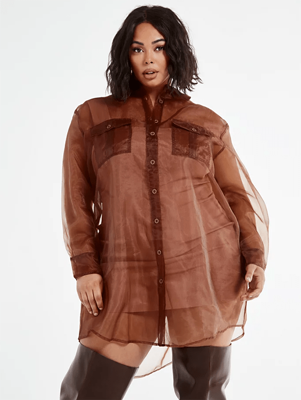 A plus-size model wearing a brown transparent button-up top, which will be marked down at Fashion to Figure's 2020 Black Friday sale.