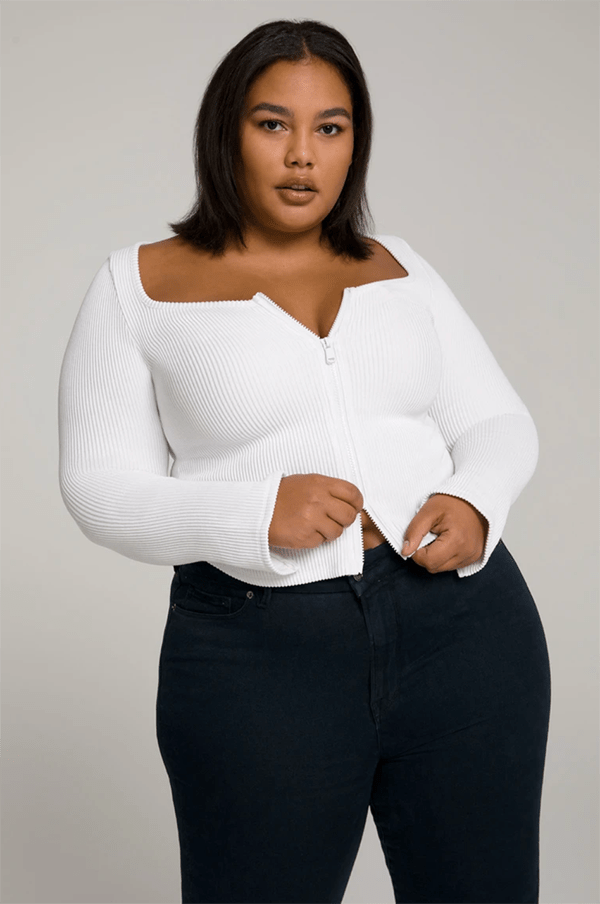 A plus-size model wearing a white top, which will be marked down at Good American's 2020 Black Friday sale.