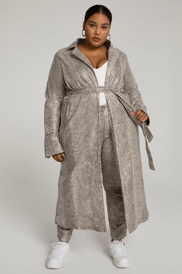 A plus-size model wearing a snakeskin trench coat, which will be marked down at Good American's 2020 Black Friday sale.