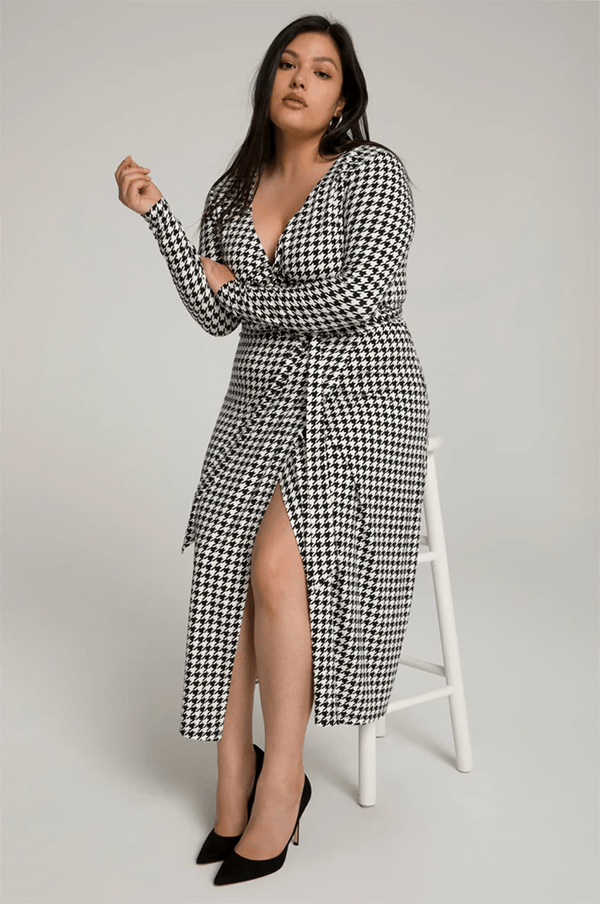 A plus-size model wearing a houndstooth wrap dress, which will be marked down at Good American's 2020 Black Friday sale.