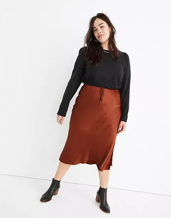 A plus-size model wearing a burnt orange satin skirt, which will be marked down at Madewell's 2020 Black Friday sale.