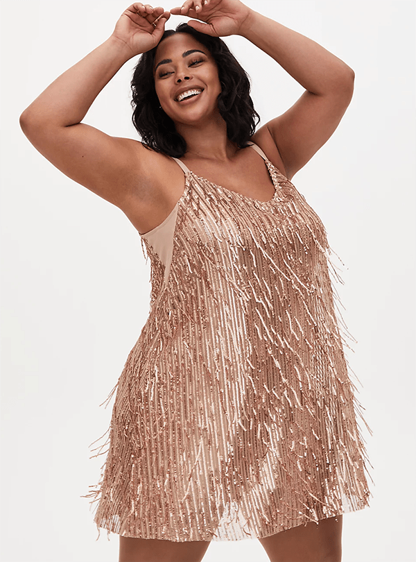 A plus-size model wearing a gold fringe dress, which will be marked down at Torrid's 2020 Black Friday sale.