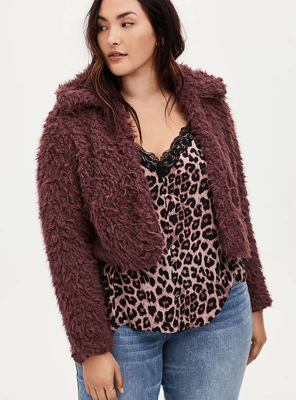 A plus-size model wearing a maroon faux fur jacket, which will be marked down at Torrid's 2020 Black Friday sale.