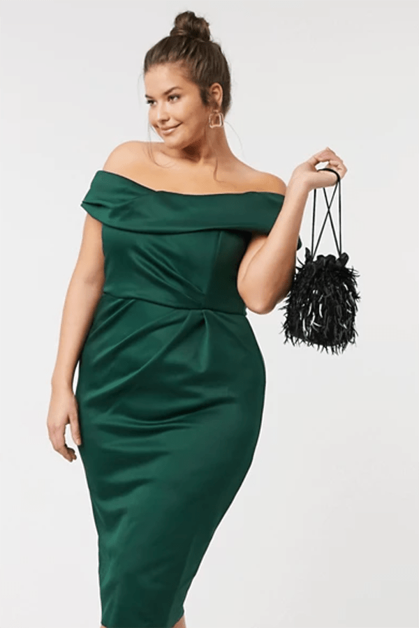 A plus size model wearing a green off-the-shoulder midi dress.