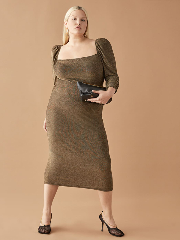A plus-size model wearing a sparkly gold holiday dress from Reformation.