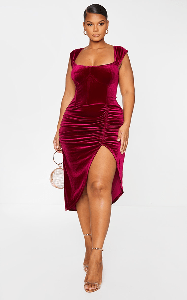 A plus-size model wearing a burgundy holiday velvet dress from PrettyLittleThing.