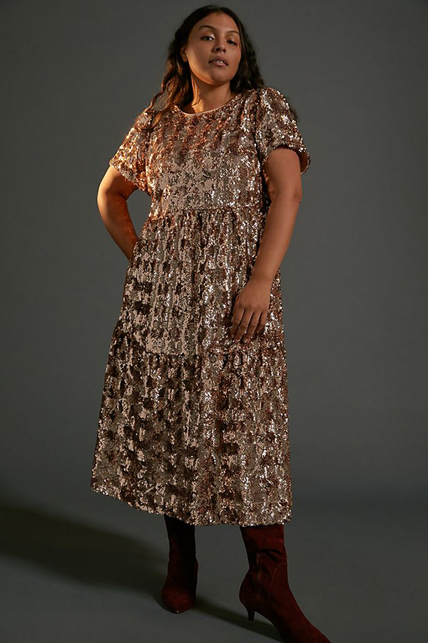 A plus-size model wearing a gold sequin holiday dress from Anthropologie.