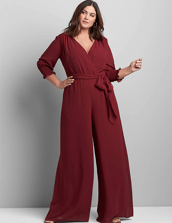 A plus-size model wearing a burgundy holiday jumpsuit from Lane Bryant.