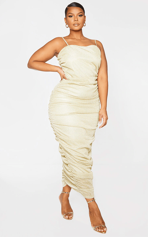 A plus-size model wearing a light gold ruched holiday dress from PrettyLittleThing.