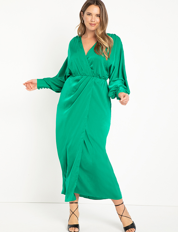 A plus-size model wearing a green holiday dress from Eloquii.
