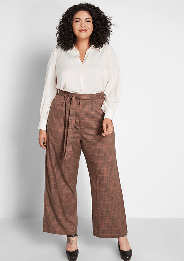 A plus-size model wearing a pair of brown wide-leg plaid pants.