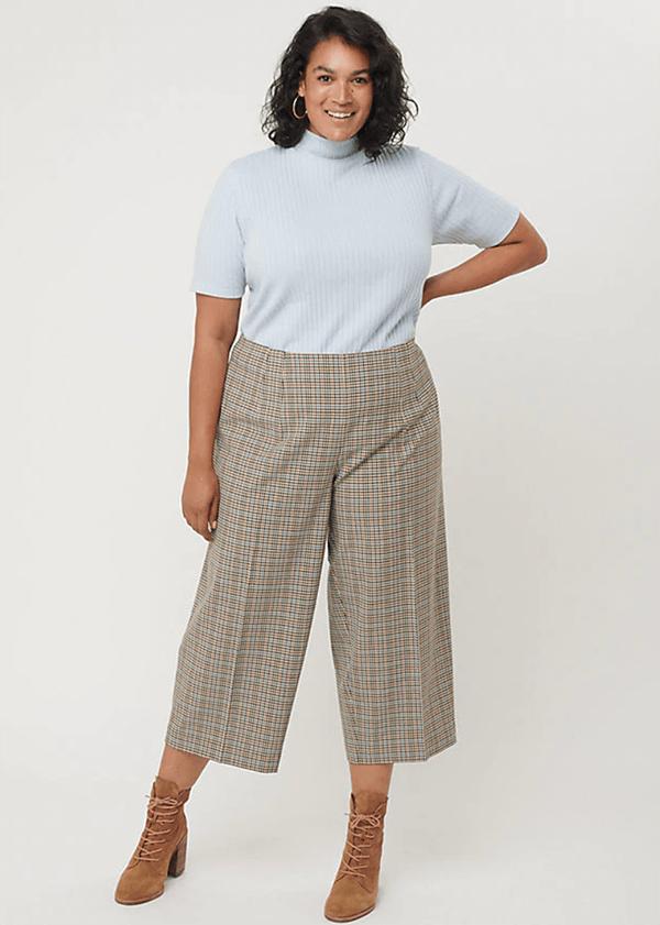 A plus-size model wearing a pair of wide-leg plaid pants.