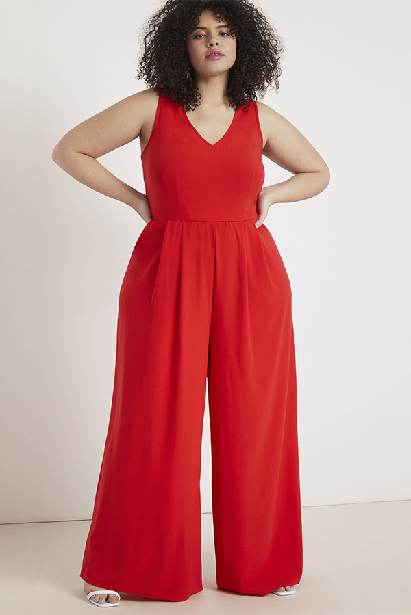 A plus-size model wearing a red palazzo jumpsuit.