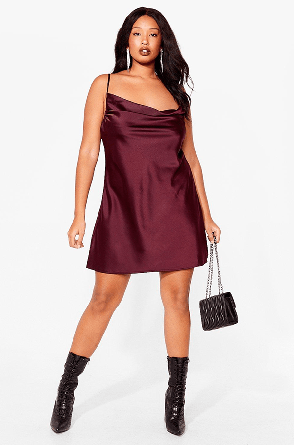 A plus-size model wearing a burgundy slip dress.