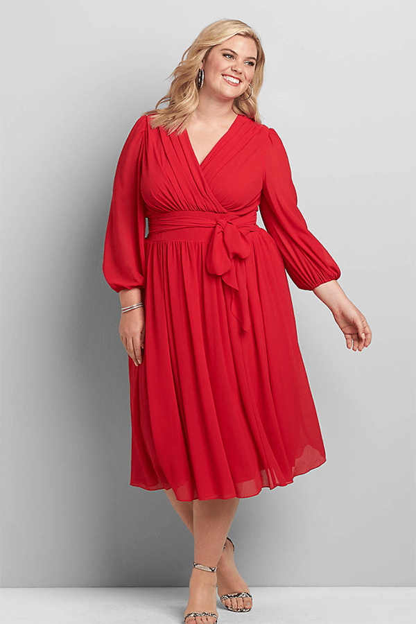 A plus-size model wearing a red midi wrap dress.