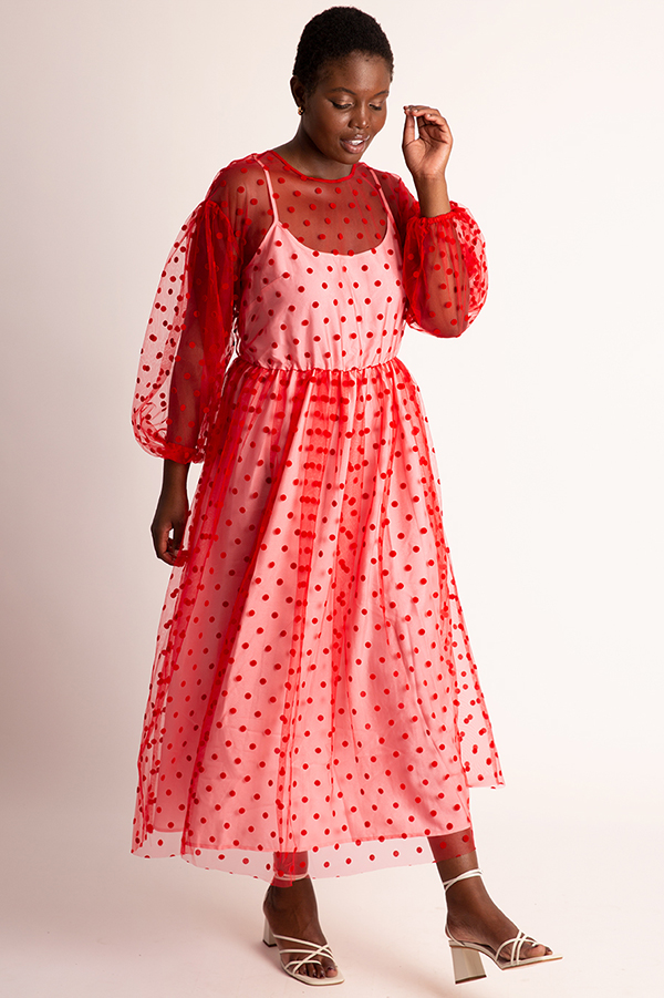 A plus-size model wearing a red polka dot midi dress.