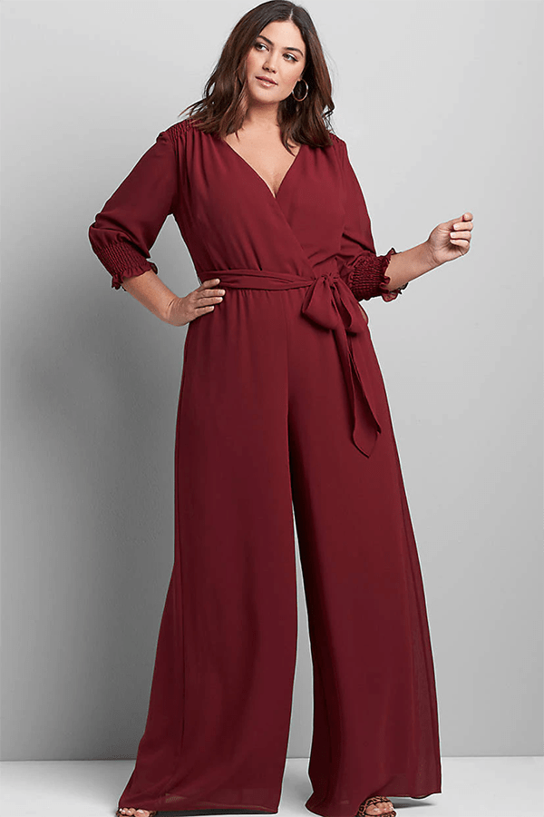 A plus-size model wearing a burgundy jumpsuit.