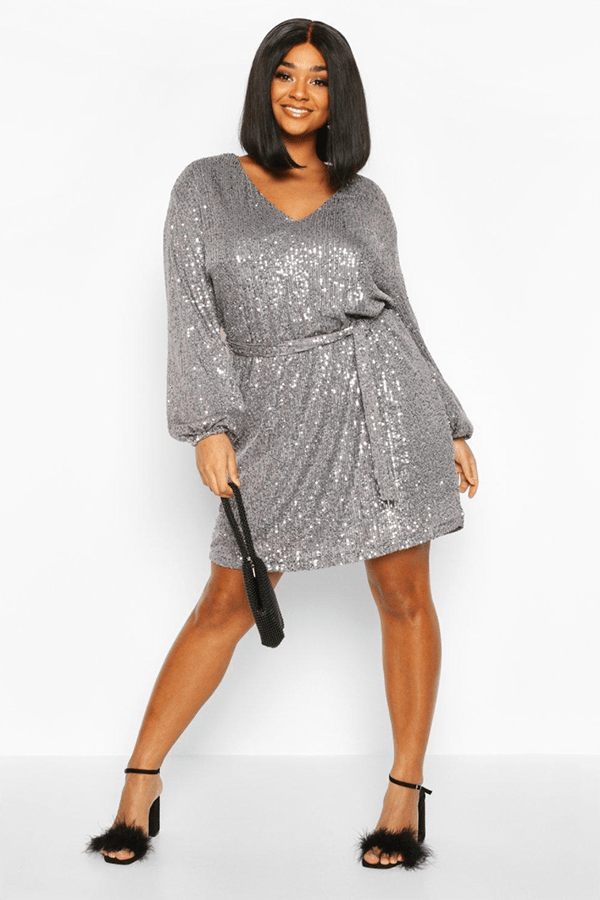 A plus-size model wearing a silver sequin dress.