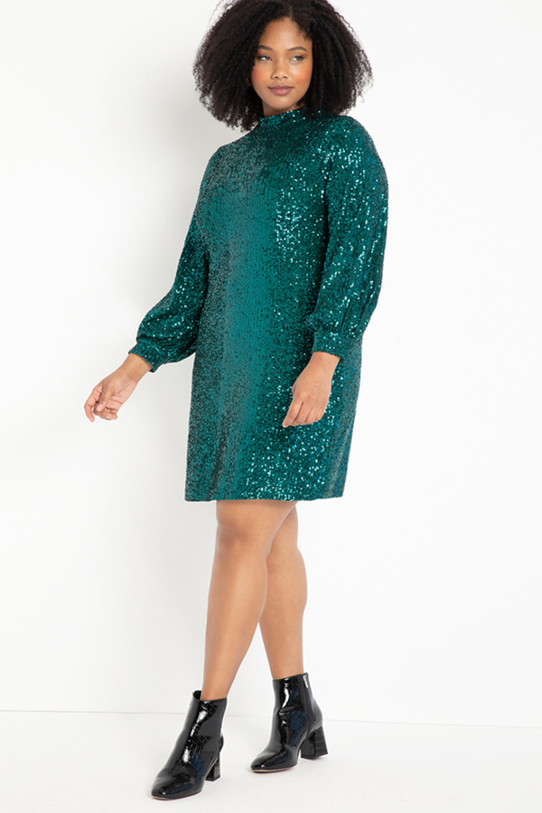 A plus-size model wearing a teal sequin shift dress.
