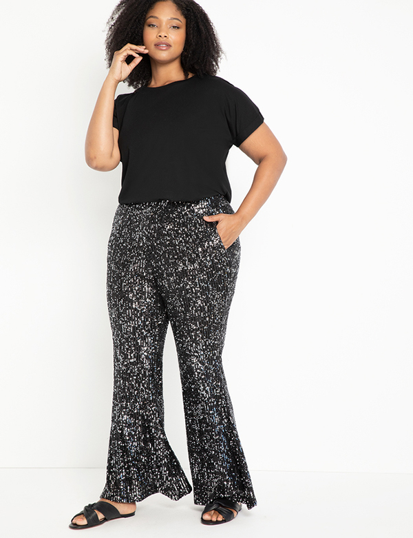 A plus-size model wearing charcoal sequin flare pants.