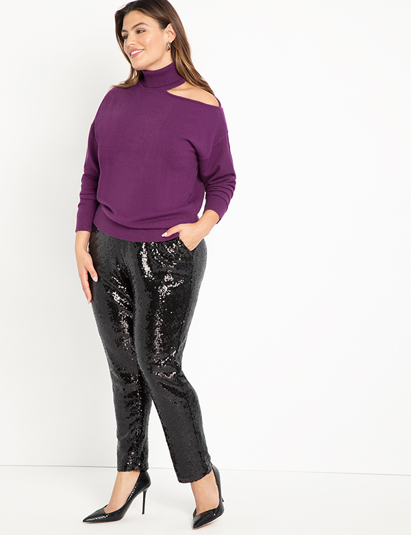 A plus-size model wearing a pair of black sequin joggers.