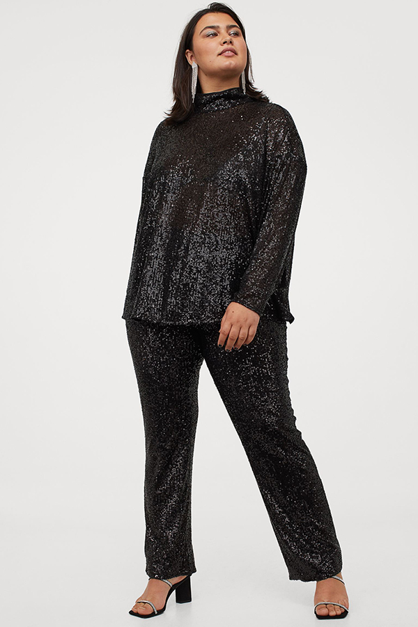 A plus-size model wearing a pair of black sequin pants.
