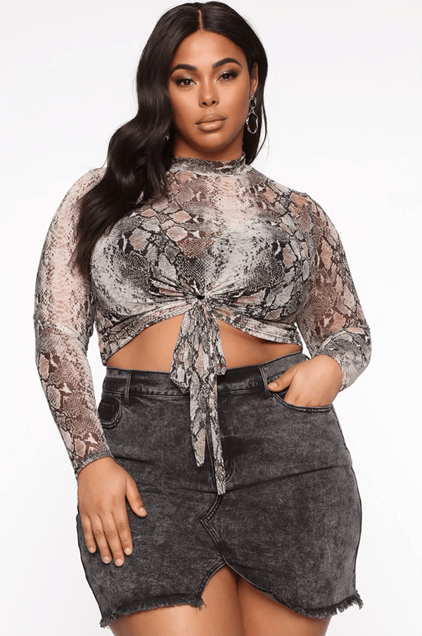 A plus-size model wearing a snake print tie-front crop top.