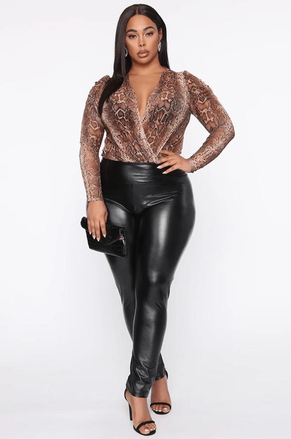 A plus-size model wearing a snake print wrap bodysuit.