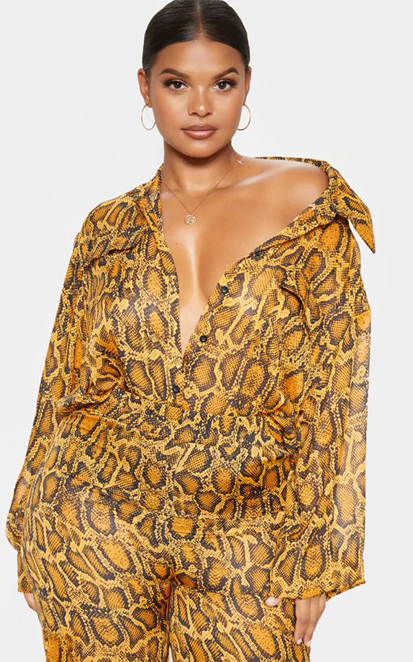 A plus-size model wearing a yellow snake print button-up shirt.