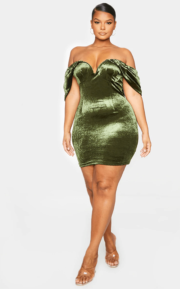 A plus-size model wearing an olive green velvet mini dress.