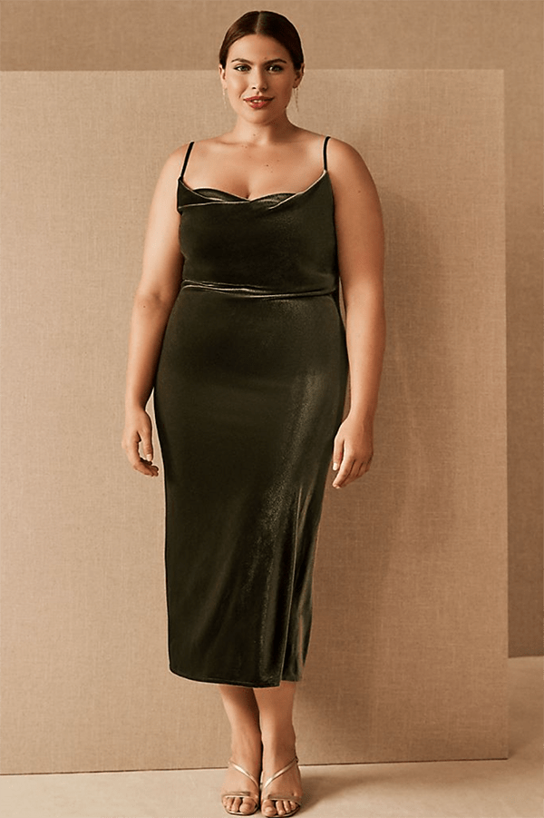 A plus-size model wearing an olive green velvet slip dress.