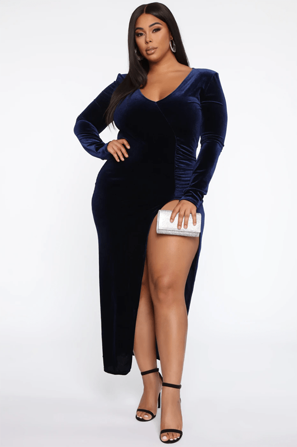 A plus-size model wearing a navy velvet maxi dress.