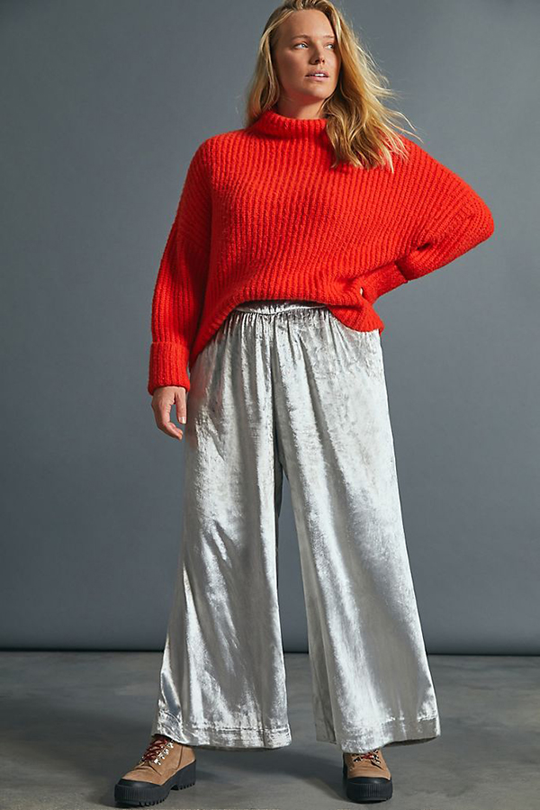 A plus-size model wearing white wide-leg velvet pants.