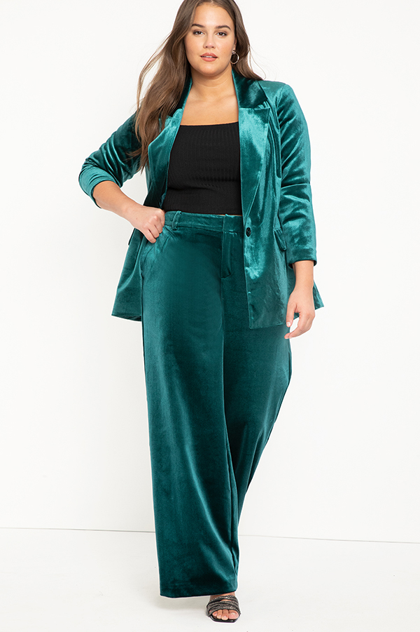 A plus-size model wearing teal wide-leg velvet pants.