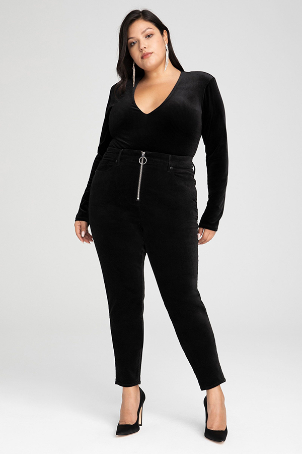 A plus-size model wearing black skinny velvet pants.