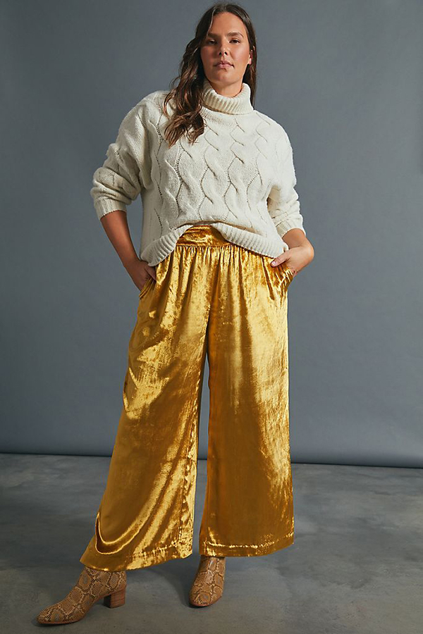 A plus-size model wearing yellow wide-leg velvet pants.