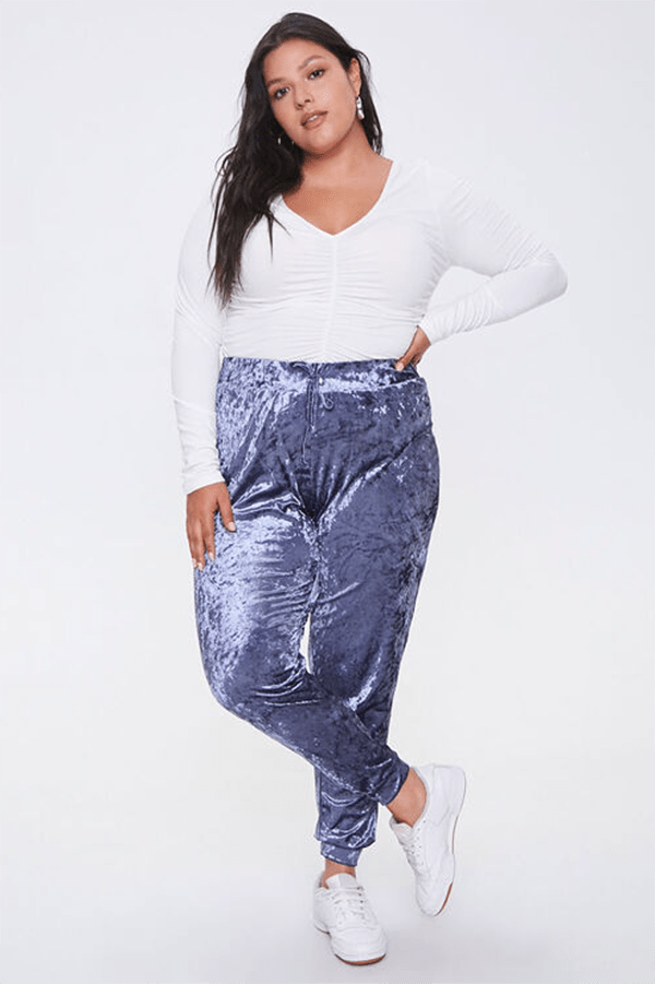 A plus-size model wearing periwinkle velvet joggers.