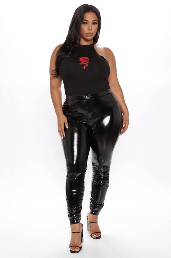 A plus-size model wearing black vinyl leggings.