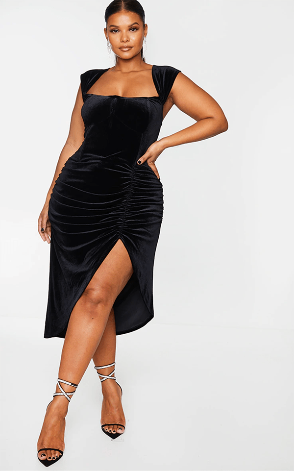 A plus-size model wearing a black velvet dress, which will be marked down at PrettyLittleThing's Black Friday 2020 sale.