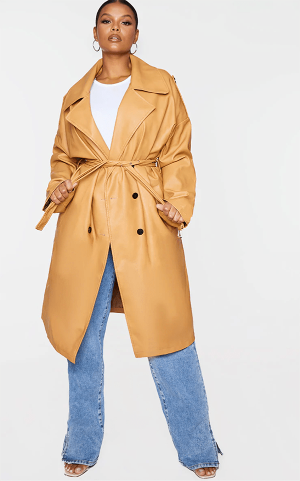A plus-size model wearing a tan trench coat, which will be marked down at PrettyLittleThing's Black Friday 2020 sale.