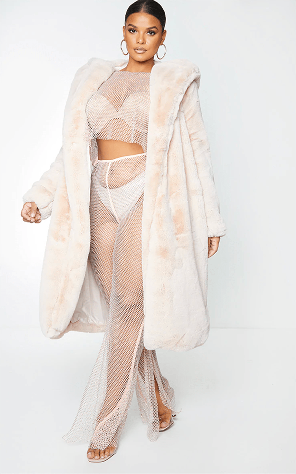 A plus-size model wearing a light pink faux fur coat, which will be marked down at PrettyLittleThing's Black Friday 2020 sale.