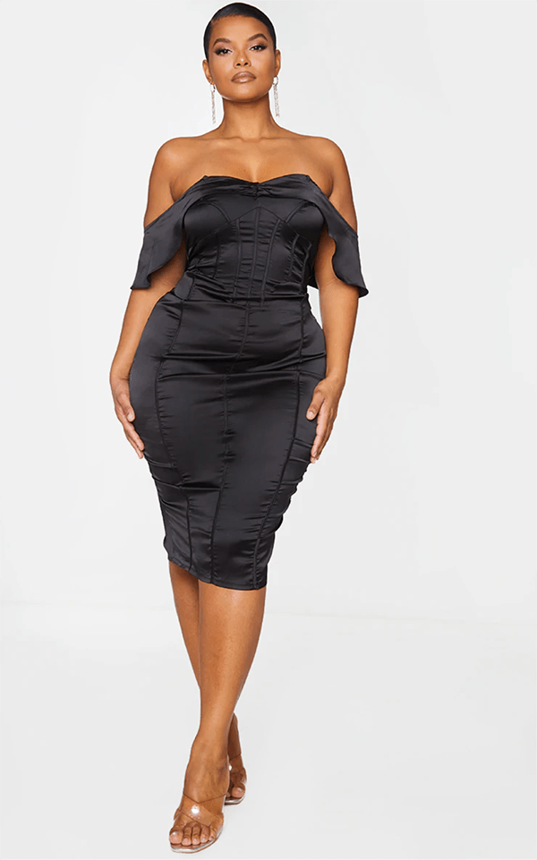 A plus-size model wearing a black satin dress, which will be marked down at PrettyLittleThing's Black Friday 2020 sale.