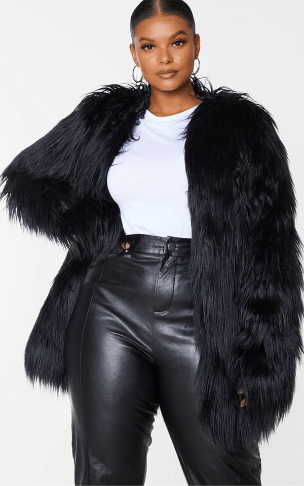 A plus-size model wearing a black faux fur coat, which will be marked down at PrettyLittleThing's Black Friday 2020 sale.