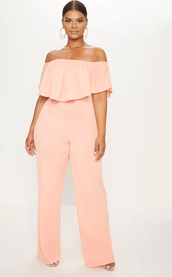A plus-size model wearing a pink off-the-shoulder jumpsuit, which will be marked down at PrettyLittleThing's Black Friday 2020 sale.