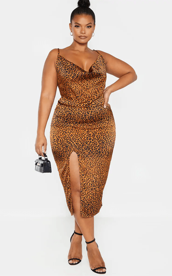 A plus-size model wearing a cheetah print satin slip dress, which will be marked down at PrettyLittleThing's Black Friday 2020 sale.