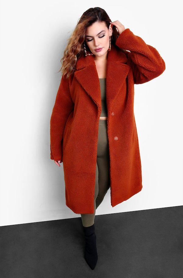 A model from Rebdolls wearing a dark orange coat.