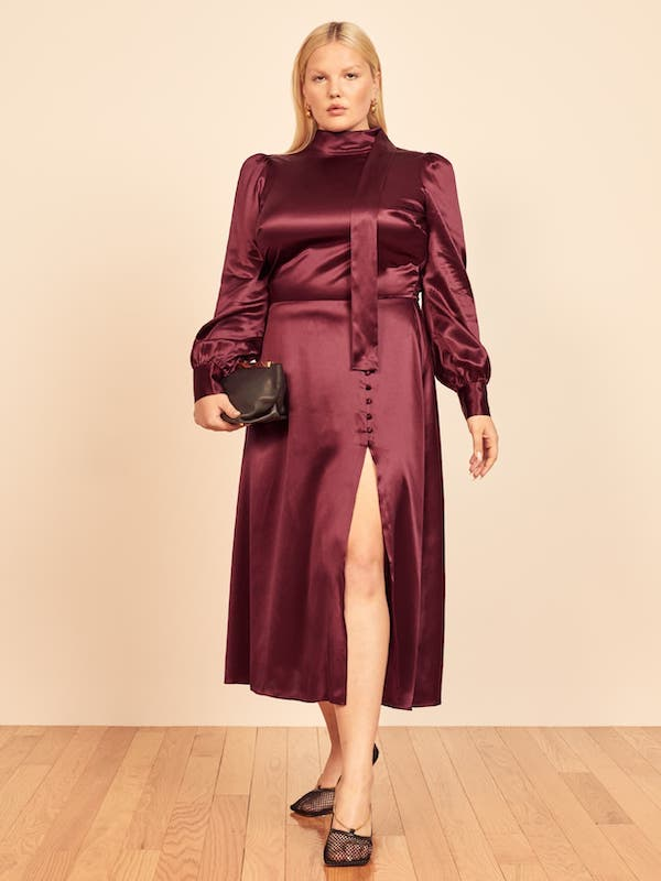 A plus-size model from Reformation wearing a wine colored satin dress.