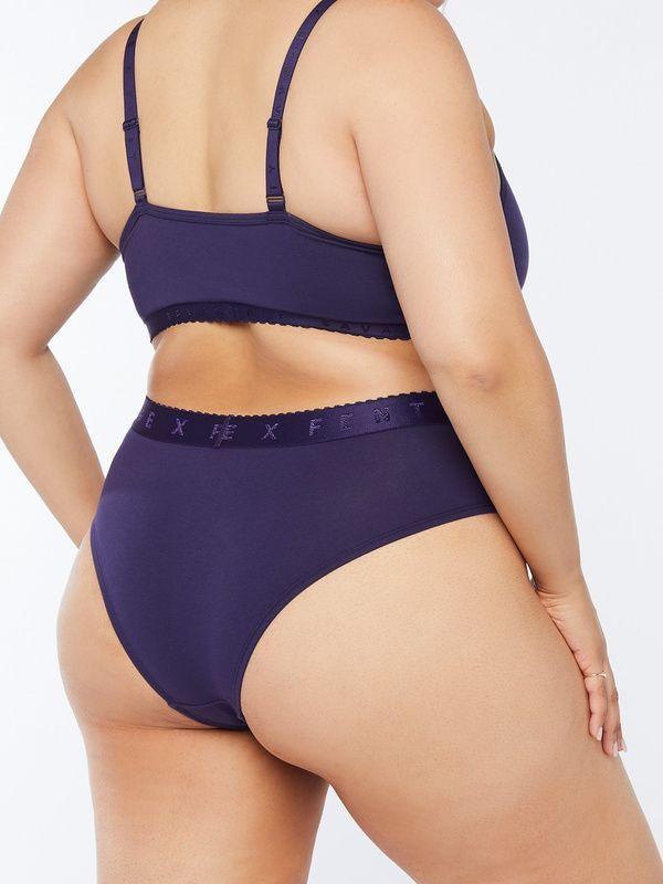 A plus-size model from Savage X Fenty wearing dark purple underwear.
