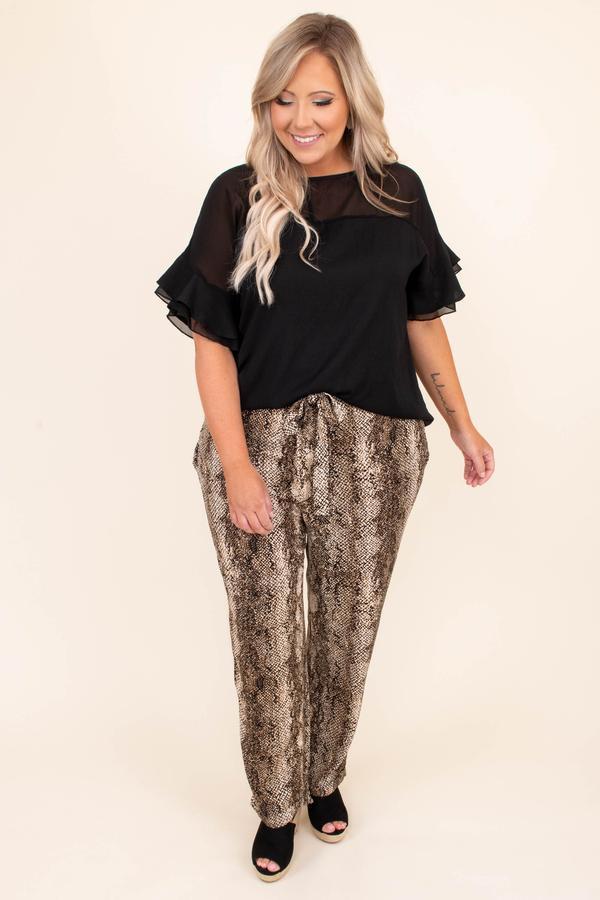 A plus-size model wearing snake print pants.