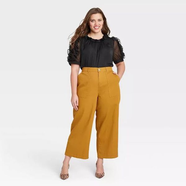 A plus-size model from Target wearing mustard yellow pants.